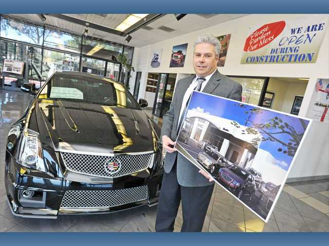 Jim Ferraccioli, executive manager of Parkway Motorcars, holds a rendering of the facade of the renovated showroom inside his group's Buick-GM-Cadillac showroom in Valencia on Monday.