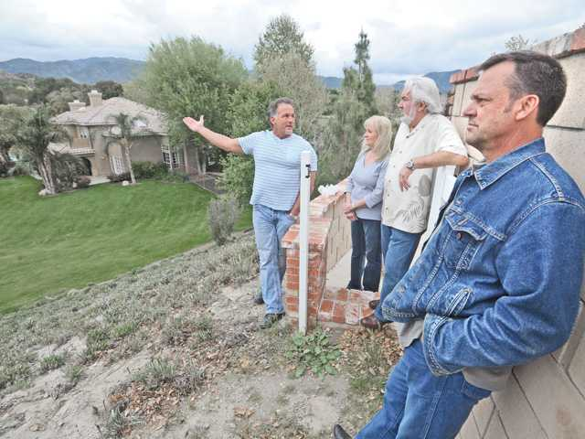 Sand Canyon residents, from left, Bill Gage, Patricia and Earl Bayless and Michael Hogan discuss the fate of Gage's home, left, and other Roadrunner Road residences, which lies in the path of a proposed high speed rail right of way.