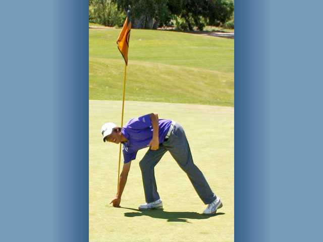 Jonathan Chang picks his ball up after a hole-in-one on No. 4  Wednesday at Robinson Ranch.