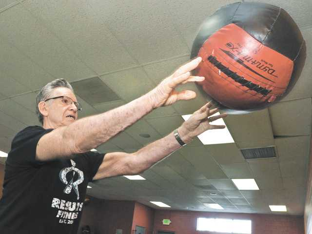 Tom Pope, 80, throws the medicine ball as part of his workout at Results Fitness gym in Newhall. Pope said he is in the best shape in years because of his new fitness routine.