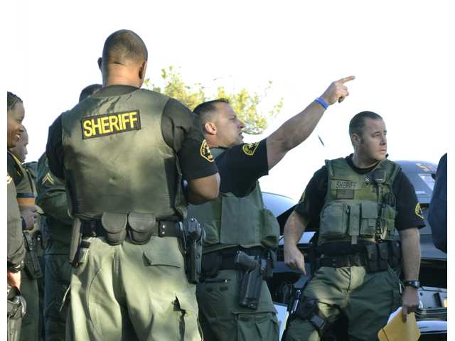 Los Angeles County Sheriff's Department deputies assigned to the department Parole Compliance Team, discuss their approach to a sweep of the Santa Clarita Valley for parolees.