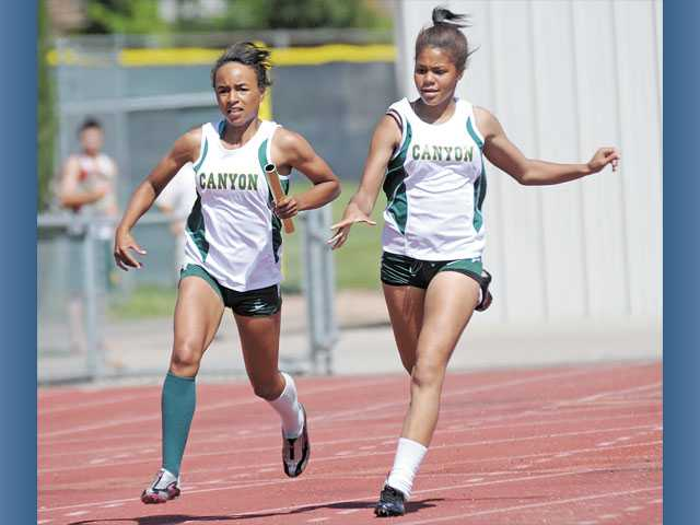 Canyon's Taylor Thomas gets the baton from Ahlexhys Hixon in the final leg of the 4x100-meter relay during a meet against Saugus on Thursday at Canyon High School. The Canyon girls defeated Saugus 87-49.