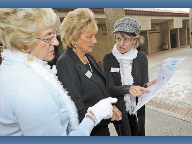 Barbara Cochran, Judy Penman and Naomi Carmona-Morshead examine paperwork.