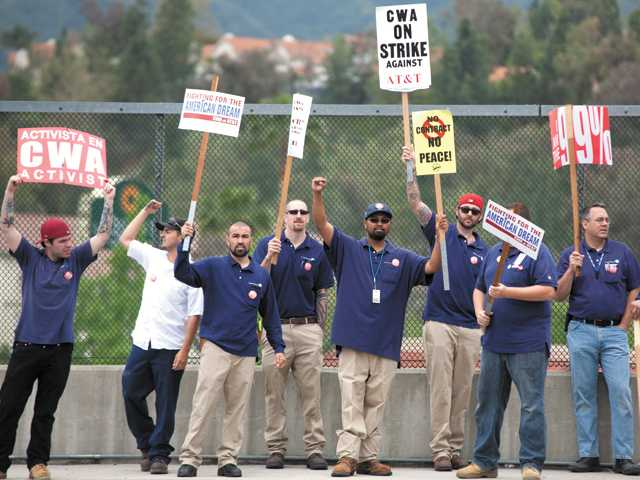 Communications Workers of America Labor 9003 union workers picket on the freeway overpass at Lyons Avenue and the Interstate 5 in Newhall on Monday.