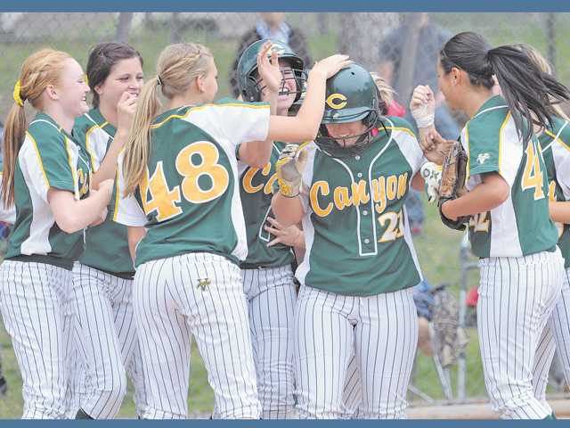 Canyon High's Courtney Ziese (21) is welcomed home in the third inning after hitting the first of two home runs against Hart on Tuesday at Newhall Park.