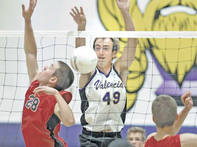 Valencia's Austin Csiszar, right, taps the ball over the net against Hart at Valencia on Tuesday.