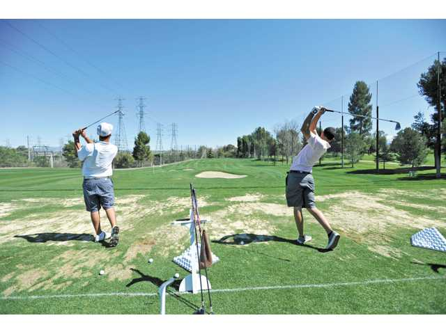 College of the Canyons golf team members practice on the driving range at Valencia Country Club in 2011.