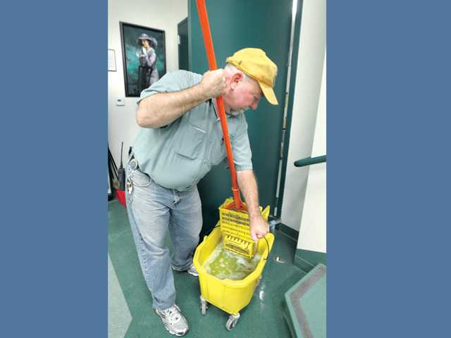 Custodian Brad Cooper wrings out his mop in front of a portrait of the school's namesake Leona H. Cox, that hangs in the cafeteria at Leona H. Cox Elementary School in Canyon Country on Wednesday.