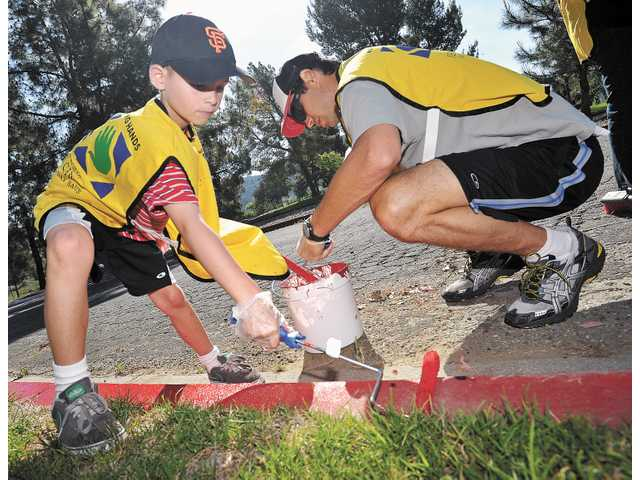 Ryan Christoffersen, 7, left, and his father, Bret, of Valencia, paint a curb in a parking lot at Castaic Lake on Saturday.