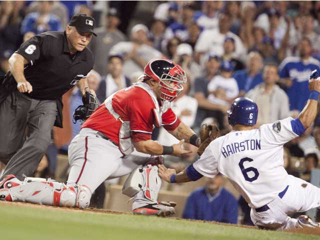 Home plate umpire Mark Carlson looks as Washington Nationals catcher Wilson Ramos tags Dodgers utility player Jerry Hairston at home plate. Ramos dropped the ball to allow Hairston to score the run during the game Saturday in Los Angeles.