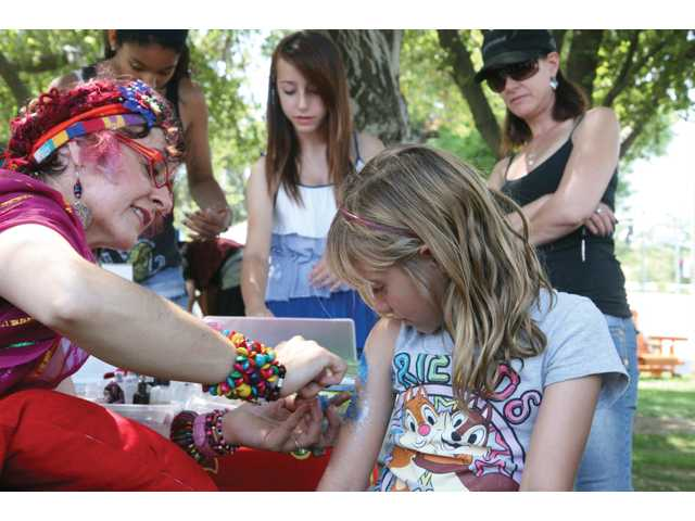 DeBra applies glitter art to the arm of Lauren Smith, 7, of Santa Clarita.