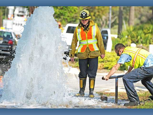 Firefighter Andrew McCombs, center, stands watch as Travis Dodd, senior utility worker with the Santa Clarita Water Division, shuts off the water flowing to a sheared fire hydrant on the 22700 block of Soledad Canyon Road in Saugus on Monday.