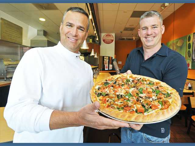 Co-owners Dan Markel, left, and Curtis Platte with a Magellan pizza at Nick-N-Willy's Pizza in Valencia. The restaurant recently won Best Overall Pizza in a cooking contest.