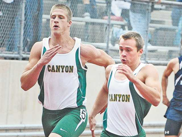 Canyon High runner Dominic Pennucci, right, overtakes teammate Drew Wolitarsky at the wire as the pair qualify in the 200 at College of the Canyons on Tuesday.