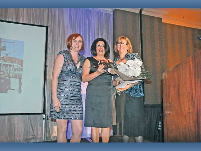 Dawn Evenson, left, and Amber Raskin, right, present the Founder's Vision Award to Ana Donovan, center.