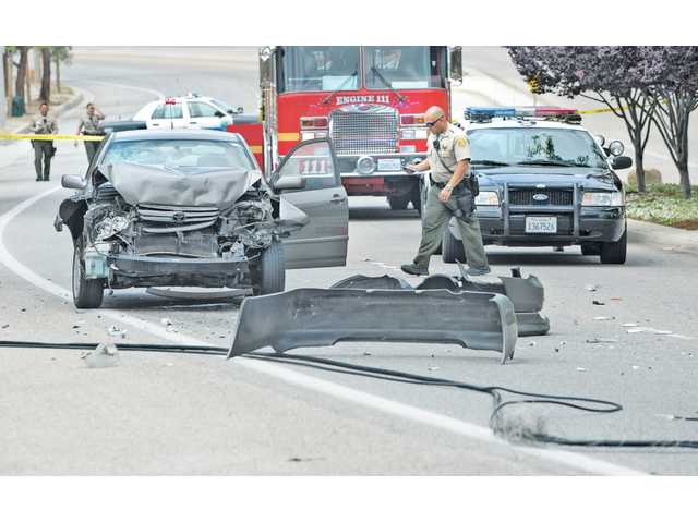 Officials assess the damage and closed the road to traffic in both directions at the scene of a traffic collision on the northbound lanes of Bouquet Canyon Road, near Susan Beth Way, where communication cables fell on the roadway in Santa Clarita.