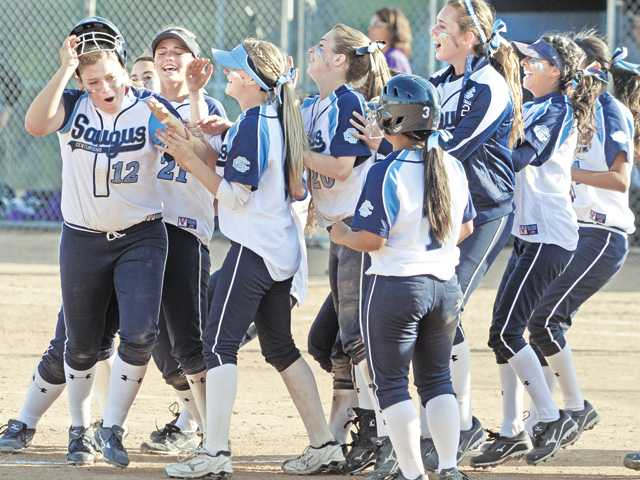 Saugus High's Alyssa Rodriguez (12) is swarmed by teammates after hitting the game-winning single against Valencia on Thursday at Saugus High School. The Centurions won the game 4-3.