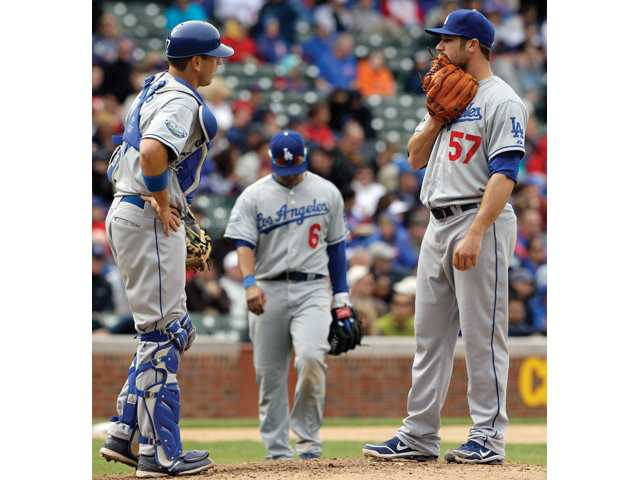 Los Angeles Dodgers relief pitcher Scott Elbert, right, talks to catcher A.J. Ellis as third baseman Jerry Hairston, center, looks down during the seventh inning of a baseball game against the Chicago Cubs in Chicago on Friday.