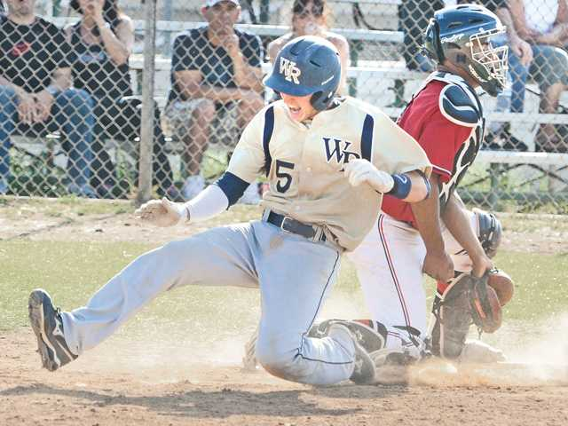 West Ranch freshman Jagger Rusconi (5) slides safely past Hart catcher Baggio Saldivar at home plate during Friday's game at Hart High School.
