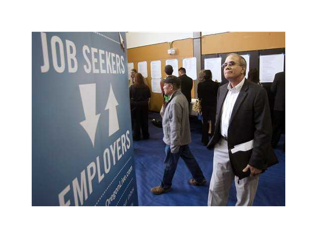n this April 24, 2012, file photo, job seeker Alan Shull attends a job fair in Portland, Ore. The Labor Department said Friday, May 4, 2012, that the economy added just 115,000 jobs in April. U.S. employers pulled back on hiring for the second straight month, evidence of an economy still growing only sluggishly.