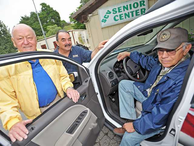 From left, volunteer drivers Glenn Grade, John Barba and Richard Szabo pose in a van in front of the Santa Clarita Valley Senior Center.