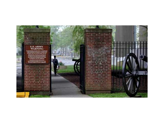A person walks towards the security gate at Fort Hamilton, in the Brooklyn borough of New York, check vehicles as they enter the base Saturday,