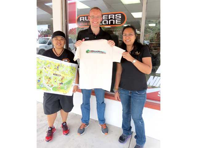 Runners Lane Manager Kyle Robinson, pictured here with store owners Flo Mina and Meliza Bautista, says sale of trail supplies and hydration equipment increased last month.