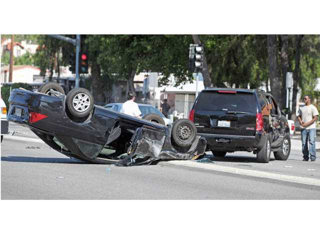A Honda Civic is seen overturned in the westbound lanes of Soledad Canyon Road near Solamint Road in Canyon Country on Monday.