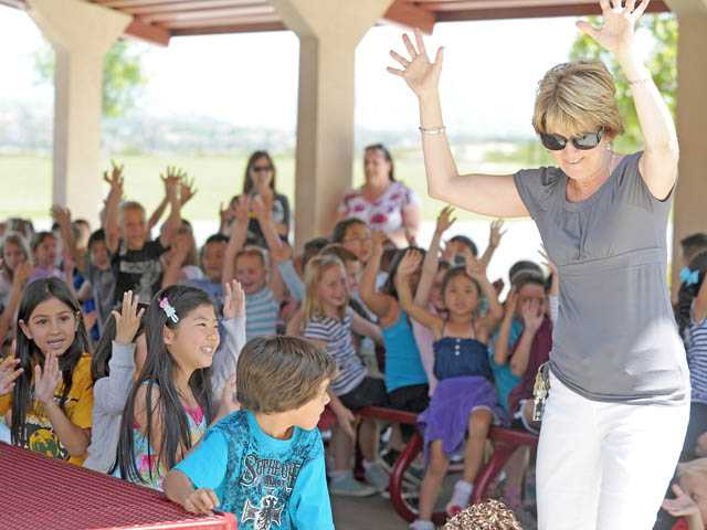 First-grade teacher Susan Karzin leads a cheer during a rally to gear up for state STAR testing at West Creek Academy in Valencia on Monday.