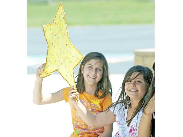 Fifth-graders Faye Saied, left, and McKenna Gambardelli cheer.