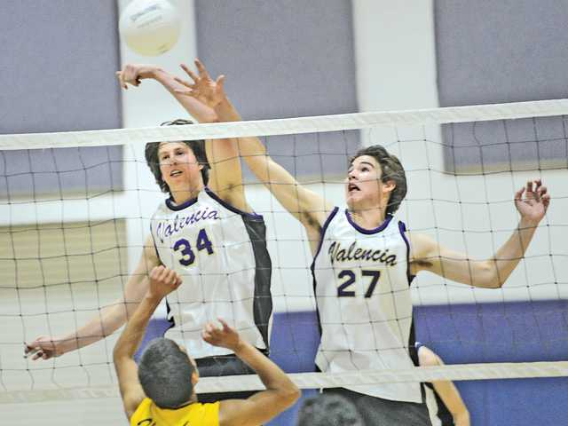 Valencia's Daniel Salovich (34) and Kyle Fults combine to block a kill attempt by Pete Knight's Victor Jacobo during the first round of the CIF-Southern Section Division II playoffs on Tuesday at Valencia High School.