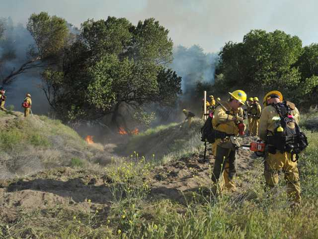 Firefighters battle a 125-acre fire in Acton on Tuesday.