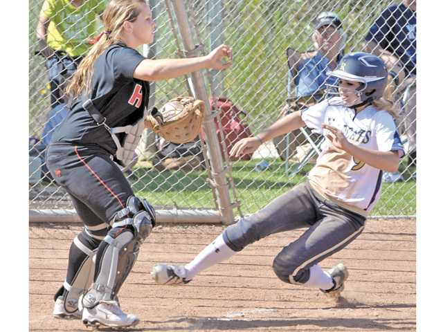 West Ranch baserunner Alissa Peterson, right, slides into home plate to score as Hart catcher Jenae Coleman waits for the throw during the first inning on Tuesday at West Ranch High.