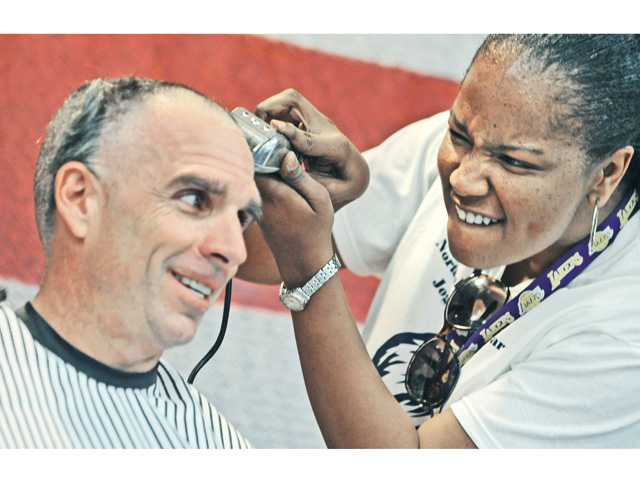 Principal Bob Brauneisen gets his head shaved (left) by fifth-grade teacher Jennetta Thomas.