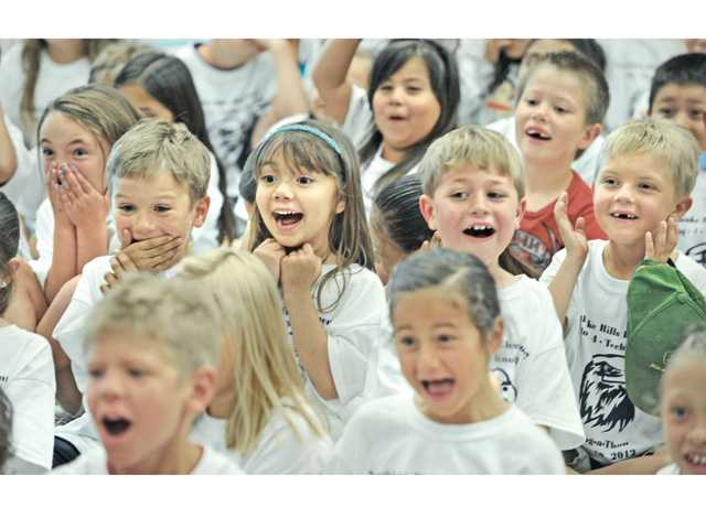 Northlake Hills Elemetary School first-graders react as Principal Bob Brauneisen gets his head shaved.