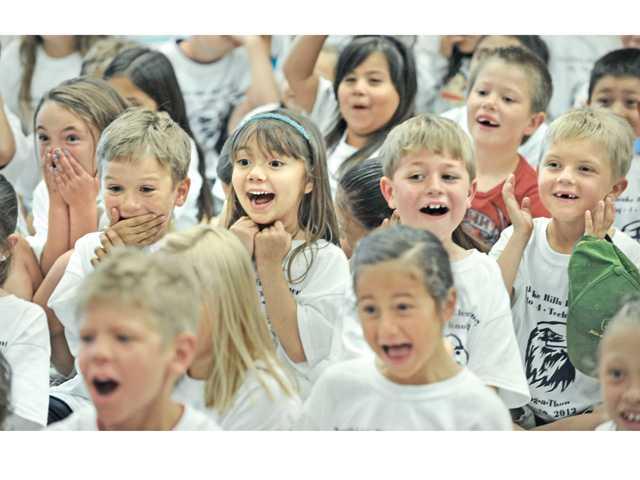 Northlake Hills Elemetary School first-graders react as Principal Bob Brauneisen gets his head shaved.