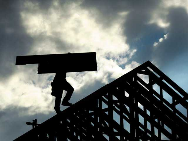 A workman carrying a piece of plywood to the peak of a roof is silhouetted against cloudy skies as construction continues on 2-story homes on the 22500 block of Breakwater Way in Santa Clarita in December.