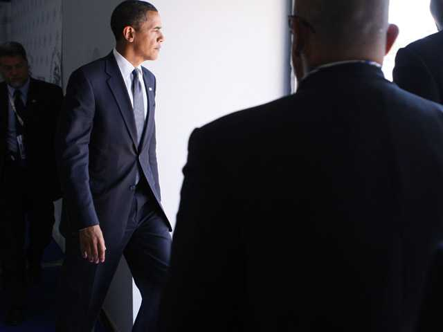 In this July 10, 2009, file photo President Barack Obama is accompanied by Secret Service agents as he leaves a press conference at the end of the G8 Summit in L'Aquila, Italy.