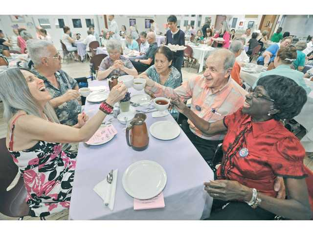 Santa Clarita Valley Senior Center volunteers Barbie Scott, left, Rudy Pavini, second right, and Tommie Ward, right, toast with cups of tea at the Volunteer Appreciation High Tea held at the SCV Senior Center in Newhall on Saturday.