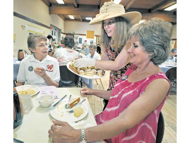 Volunteers Rita Hendrixson, left, and Stellina Parcho, right, are served sandwiches by Senior Center Associate Executive Director Linda Alexander-Lieblang.