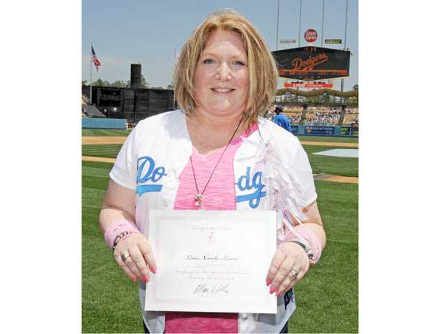 Canyon Country resident Lisa Lewis, a mother of two and breast cancer survivor, holds up a certificate of recognition at Dodger Stadium on Sunday.