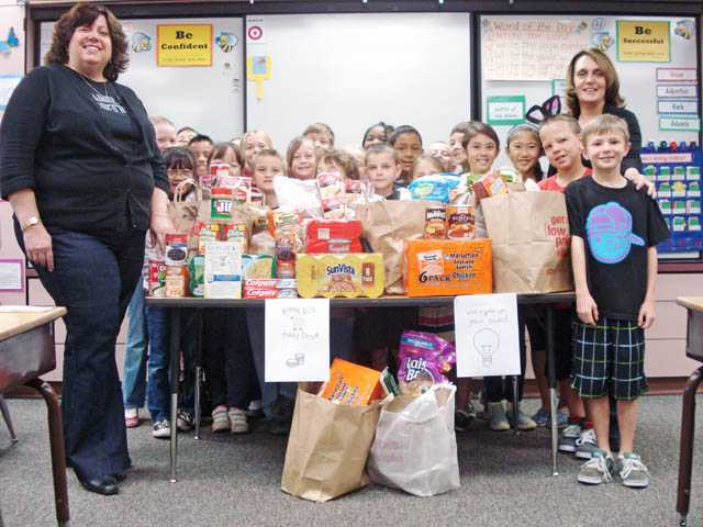 The third-grade classroom at James Foster Elementary School stands with their 15 bags of donations to the Santa Clarita Valley Food Pantry.
