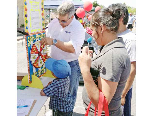 Martin Rodriguez, of Pacific Funding, helps a young visitor spin a prize wheel at the booth Rodriguez shared with Carlos Avalos of Keller Williams at the Cinco de Mayo event held on Main Street in downtown Newhall.