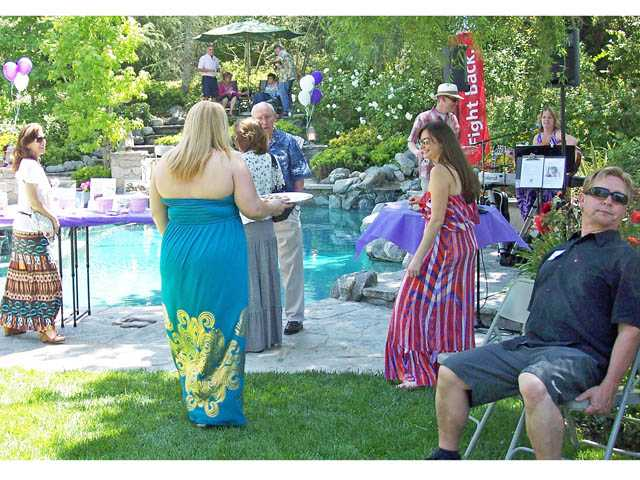 Guests mingle in the Valencia backyard of Pam and Mike Ripling during the Pop-a-cork for a Cure fundraiser to benefit the American Cancer Society. The event was hosted by Team Check 'Em Out for SCV Relay for Life.