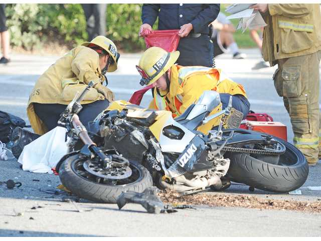 Firefighters from Fire Station 156 cover the body of a man who died at the scene of a motorcycle crash at the corner of Decoro Drive and Rutherford Place in North Valencia on Thursday. The fatal crash marks the third rider killed in less than two weeks in the Santa Clarita Valley.