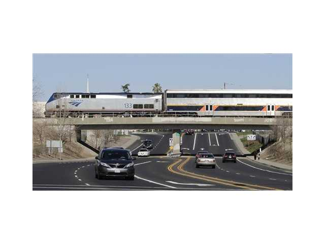 In this photo taken Feb. 14, an Amtrak train bound for the San Francisco Bay Area travels through West Sacramento. The state Legislative Analyst's Office, said the latest proposal to build a $68.4 billion high-speed train system is still too vague.