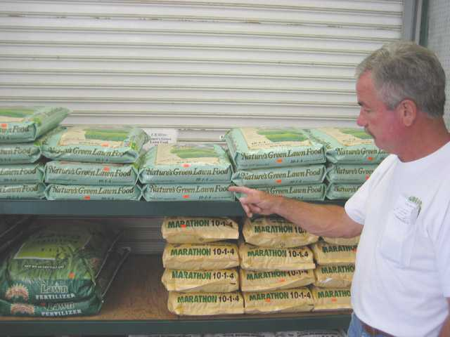 Richard Green of Green Landscape Nursery points out the Nature's Green organic lawn fertilizer which helps lawns grow thick and hardy, which helps retain moisture.