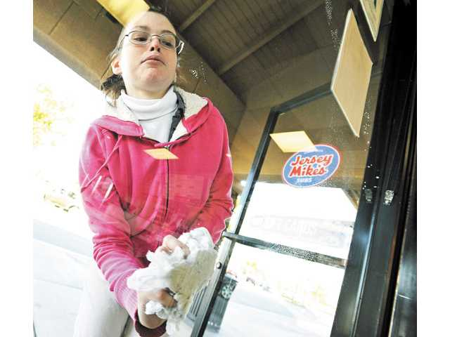Becky Anderson, 28, cleans a window before the opening at Jersey Mike's in Saugus on Thursday.