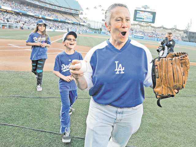 Santa Clarita resident Sheri Griffin, right, celebrates her ceremonial first pitch with son Zachary Griffin, middle, and daughter Melissa Griffin as part of Santa Clarita Dodger Day at Dodger Stadium in Los Angeles on Saturday. Before the game, the family was chosen at random from more than 1,000 SCV fans who showed up to the event.