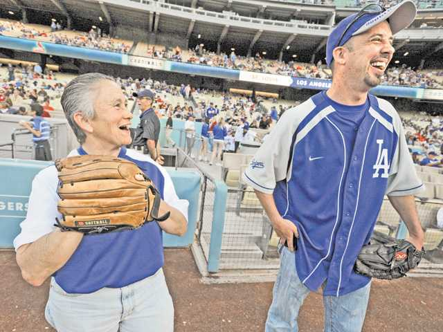 Sheri Griffin, left, and Scott Cusack, who participated as the catcher in the ceremonial first pitch, spend a moment on the field during Santa Clarita Dodger Day festivities at Dodger Stadium in Los Angeles on Saturday.